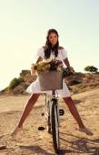Beautiful smiling girl riding a bicycle along the sea coast — Stock Photo