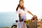 Pretty smiling girl with dark hair in elegant dress sitting on bicycle — Stock Photo