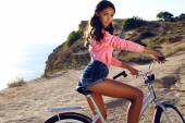 Pretty girl with dark hair in sport clothes sitting on bicycle  — Stock Photo