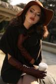 Beautiful girl in elegant coat and hat drinking coffee at park — Stock Photo