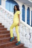 Beautiful model with black hair wearing elegant yellow suit — Stock Photo