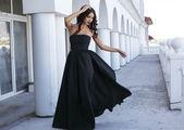 Beautiful woman with dark hair in elegant black dress — Stock Photo