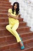 Beautiful woman with black hair in elegant yellow suit — Foto de Stock