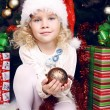 Cute little girl in Santa's hat sitting beside a Christmas tree — Stock Photo #56734079