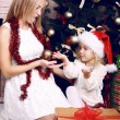 Cute little girl in Santa's hat playing with her mother beside a christmas tree — 图库照片 #56734111