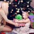 Funny little girl with her mom posing beside a christmas tree and presents — Stock Photo #56734333