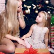 Cute little emotional girl with her mom posing beside a Christmas tree — Stock Photo #56734335