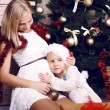 Tender photo of little girl with her pregnant mother beside a Christmas tree — Stock Photo #56734473
