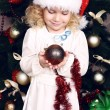 Cute little girl in Santa's hat decorating Christmas tree — Foto Stock #56737873