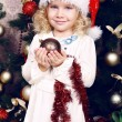 Cute little girl in Santa's hat decorating Christmas tree — Stock Photo #56737935