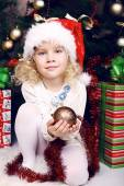 Cute little girl in Santa's hat sitting beside a Christmas tree — Stock Photo
