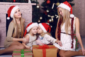 Happy family posing beside a decorated Christmas tree — Stock fotografie
