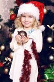 Cute little girl in Santa's hat decorating Christmas tree — Stock Photo