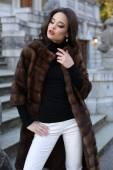 Beautiful woman with dark hair in luxurious fur coat posing on stairs — Stockfoto