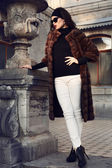 Beautiful elegant woman in luxurious fur coat posing in castle — Stock Photo