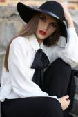 Portrait of beautiful girl with dark hair in elegant blouse and hat — Stock Photo