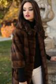 Beautiful woman with dark hair in luxurious fur coat posing at park — Stock Photo
