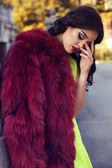 Beautiful woman with dark hair wearing luxurious red fur — Stockfoto