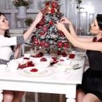 Beautiful sisters decorating Christmas tree at home — Stock Photo #56987779