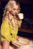 Sexy woman reading book and drinking tea beside a chimney — Stock Photo