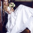 Beautiful bride with blond hair in luxurious dress with wedding flowers — Stock Photo #60519969