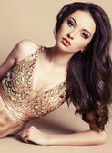 Beautiful girl with dark hair in luxurious sequin dress — Stock Photo