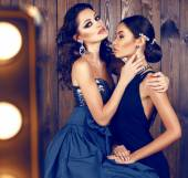 Two beautiful women with dark hair in luxurious dresses — Stock Photo