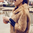 Sexy blond woman wearing luxurious fur coat and sunglasses — Stock Photo #60770771