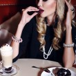 Gorgeous woman with blond hair sitting in cafe with coffee and dessert — Stock Photo #62585113