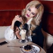 Gorgeous woman with blond hair sitting in cafe with coffee and dessert — Stock Photo #62585363