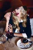 Gorgeous woman with blond hair in elegant suit and hat,sitting in cafe — Stock Photo