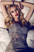 Gorgeous woman with blond hair in elegant dress lying on divan   — Stock Photo