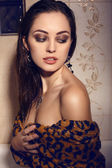Beautiful woman with dark hair wearing elegant leopard print robe and bijou   — Stock Photo