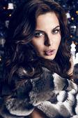 Sensual woman with dark hair in luxurious fur coat — Stock Photo