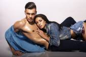 Sexy impassioned couple in jeans clothes posing in studio   — Stock Photo
