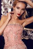 Blond woman in elegant sequin dress posing in luxurious interior — Stock Photo