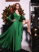Pretty woman in elegant green dress posing in luxurious interior — Stockfoto