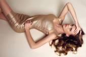 Beautiful sensual woman with dark hair in elegant gold dress   — Stock Photo