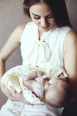 Beautiful young mother with long dark hair posing with her little adorable baby — Stock Photo