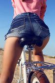 Jambes de femme en short jeans assis sur le vélo — Photo