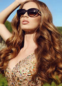Sensual woman with long red hair in luxurious sequin dress with sunglasses   — Stock Photo