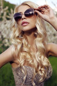 Sensual blond girl  in luxurious sequin dress with sunglasses  — Stock Photo