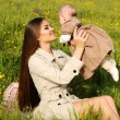 Beautiful mother having fun with her little cute baby in summer garden — Stock Photo #73414327