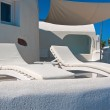 Two longue chairs on terrace of Oia at Santorini, Greece — Stock Photo #60861573