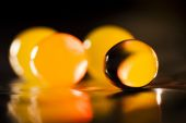 Abstract composition with beautiful, orange, round jelly balls on an aluminium foil with reflexions and dark background — Stock Photo