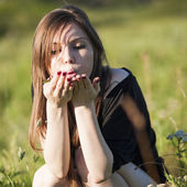 Beautiful girl with long, straight hair posing in the field looking melancholic — Stock Photo
