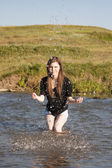 Beautiful girl with long, straight hair posing and playing with water in a small river — Photo