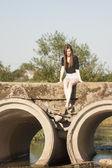 Hermosa chica con el pelo largo, recto, posando y jugando en un puente de hormigón sobre un pequeño río — Foto de Stock