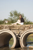 Beautiful girl with long, straight hair posing and playing on a concrete bridge over a small river — Stock Photo