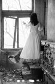 Sad mood in an old, abandoned house with girl wearing an old fashioned wedding dress with natural light. Photo has grain texture visible on its maximum size. Artistic black and white photography — Stock Photo